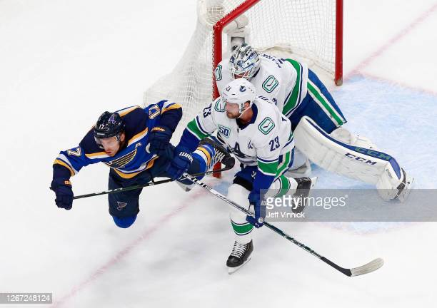 Alexander Edler of the Vancouver Canucks trips up Jaden Schwartz of the St. Louis Blues during the first period in Game Five of the Western...