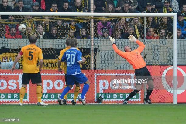 Alexander Esswein of Dresden scores his team's first goal against goalkeeper Axel Keller of Rostock during the Third League match between Dynamo...
