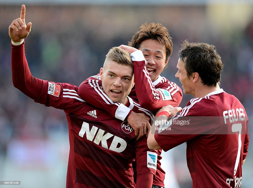 Alexander Esswein (L) of Nuernberg celebrates with Hiroshi Kiyotake (C) and Markus Feulner after scoring his team's second goal during the Bundesliga match between 1. FC Nuernberg and FC Schalke 04 at Grundig-Stadion on March 16, 2013 in Nuremberg, Germany.