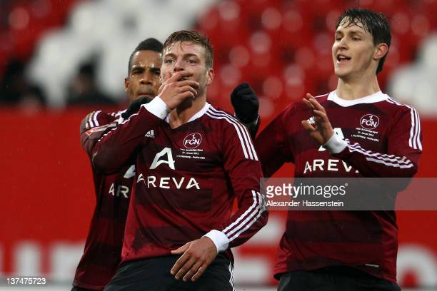 Alexander Esswein of Nuernberg reacts after scoring the opening goal wiith his team mates Daniel Didavi and Philipp Wohlscheid during the Bundesliga...