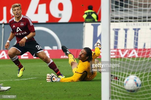 Alexander Esswein of Nuernberg scores his team's first goal against goalkeeper Simon Jentzsch of Augsburg during the Bundesliga match between 1 FC...