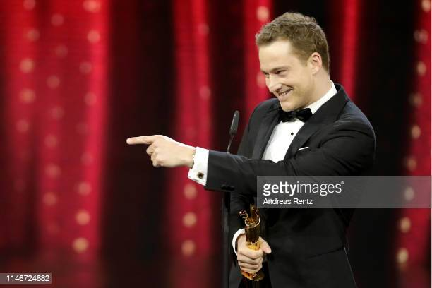 Alexander Fehling, winner best male supporting role, reacts on stage during the Lola - German Film Award show at Palais am Funkturm on May 03, 2019...