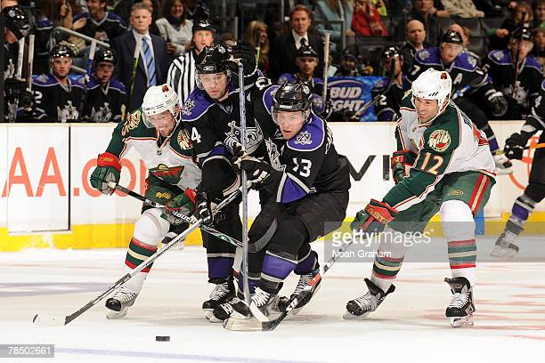 Alexander Frolov and Michael Cammalleri of the Los Angeles Kings battle for the puck against Eric Belanger and Brian Rolston of the Minnesota Wild at...