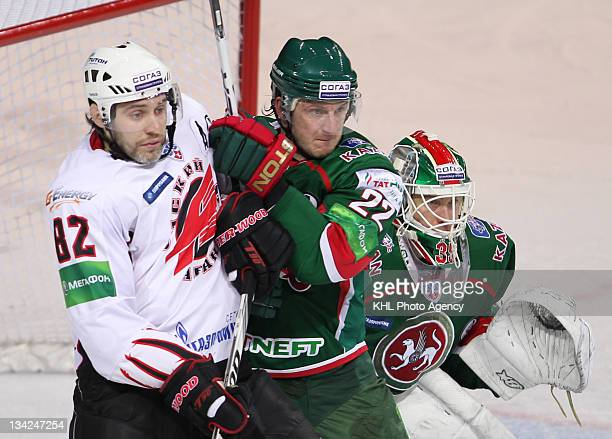 Alexander Frolov of the Avangard Konstantin Korneyev and goaltender Petri Vehanen of the Ak Bars watches for the attack during the game between...