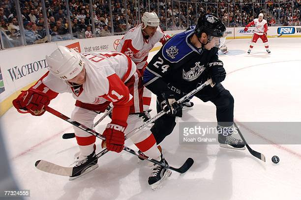 Alexander Frolov of the Los Angeles Kings battles for the puck against Dan Cleary and Chris Chelios of the Detroit Red Wings during the first period...