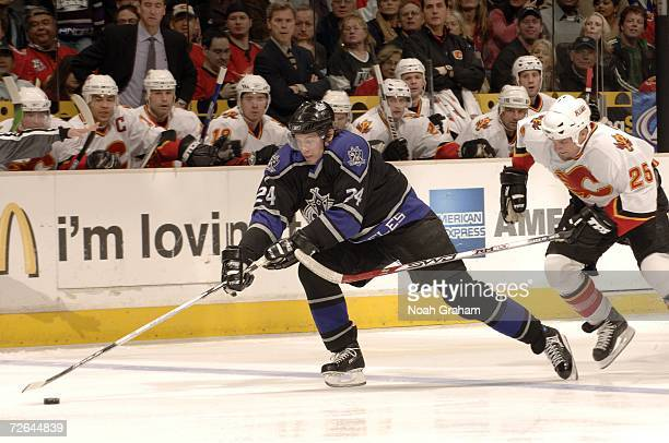Alexander Frolov of the Los Angeles Kings carries the puck against Darren McCarty of the Calgary Flames on November 25 2006 at the Staples Center in...