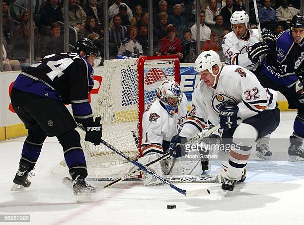 Alexander Frolov of the Los Angeles Kings fights for the puck against Matt Greene of the Edmonton Oilers on January 26 2006 at the Staples Center in...