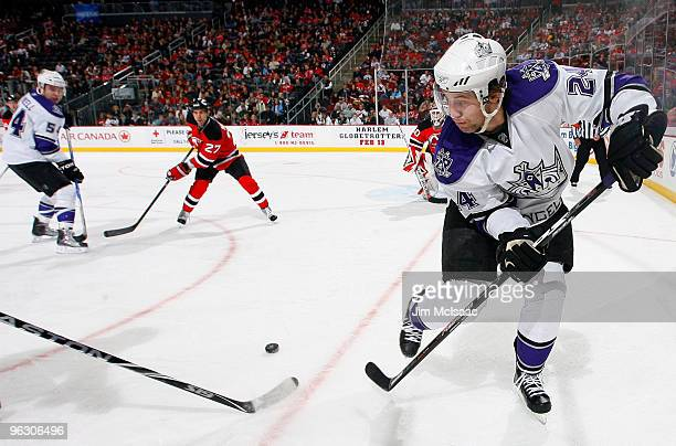 Alexander Frolov of the Los Angeles Kings passes the puck to teammate Teddy Purcell as Mike Mottau of the New Jersey Devils looks on at the...