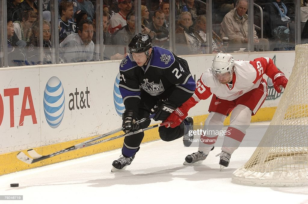Alexander Frolov #24 of the Los Angeles Kings reaches for the puck alongside the boards against Niklas Kronwall #55 of the Detroit Red Wings on January 22, 2008 at the Staples Center in Los Angeles, California