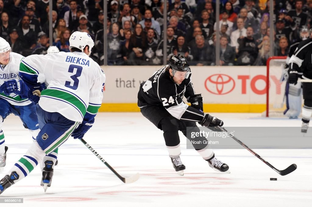 Alexander Frolov #24 of the Los Angeles Kings skates with the puck against Kevin Bieksa #3 of the Vancouver Canucks in Game Three of the Western Conference Quarterfinals during the 2010 NHL Stanley Cup Playoffs at Staples Center on April 19, 2010 in Los Angeles, California.