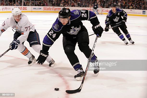 Alexander Frolov of the Los Angeles Kings skates with the puck against Tom Gilbert of the Edmonton Oilers on April 10 2010 at Staples Center in Los...