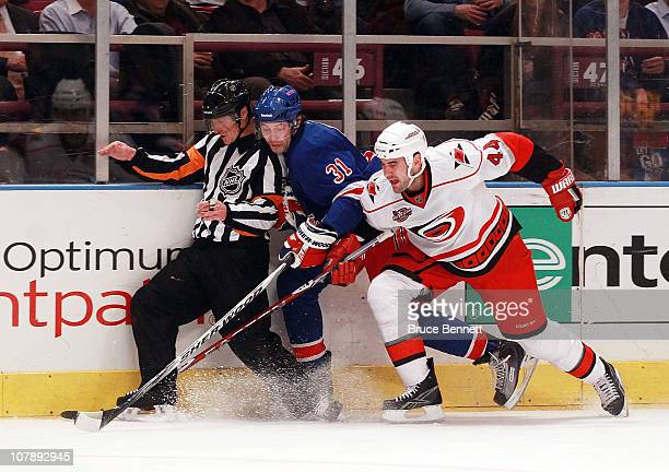Alexander Frolov of the New York Rangers and Jay Harrison of the Carolina Hurricanes collide along the boards with referee Rob Martell at Madison...