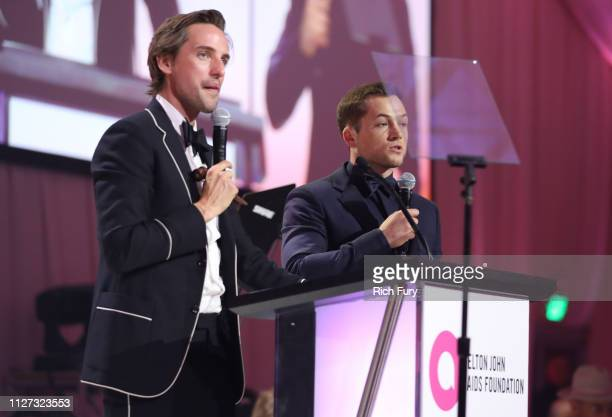 Alexander Gilkes and Gus Kenworthy speak on stage at the 27th annual Elton John AIDS Foundation Academy Awards Viewing Party sponsored by IMDb and...