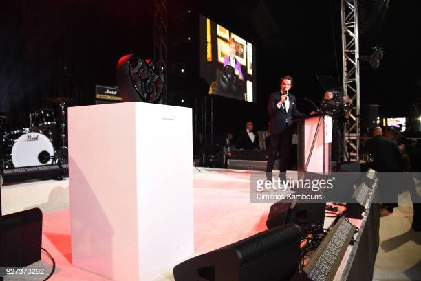 Alexander Gilkes leads an auction during the 26th annual Elton John AIDS Foundation Academy Awards Viewing Party sponsored by Bulgari celebrating...
