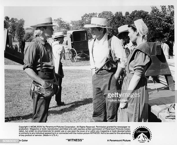 Alexander Godunov gives advice to Harrison Ford and Kelly McGillis in a scene from the Paramount Pictures movie Witness circa 1985