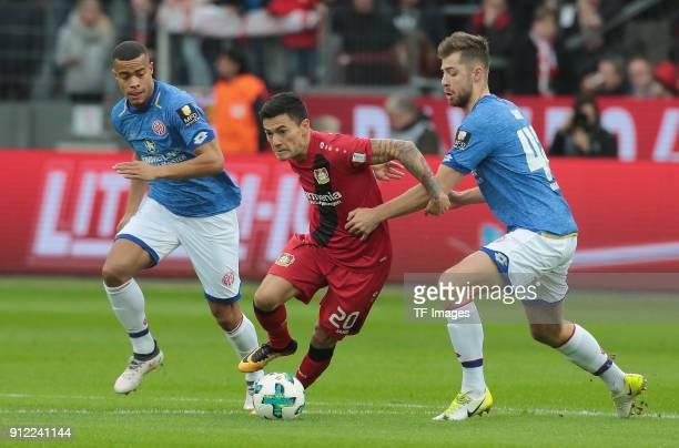 Alexander Hack of Mainz Charles Aranguiz of Leverkusen and Abdou Diallo of Mainz battle for the ball during the Bundesliga match between Bayer 04...