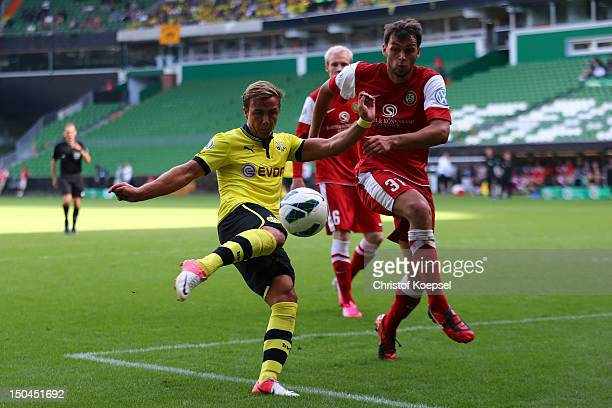 Alexander Hessel of Oberneuland challenges Mario Goetze of Dortmund during the first round DFB Cup match between FC Oberneuland and Borussia Dortmund...