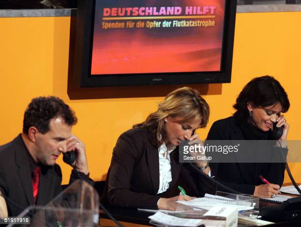 Alexander Hold Caroline Beil and Gerit Kling take phone calls from donors at the live broadcast of the SAT1 telethon benefit Germany Helps...