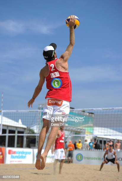 Alexander Huber of Austria serves to Pablo Herrera of Spain during the men's Transavia Grand Slam beach volleyball match on July 17 2014 in The Hague...