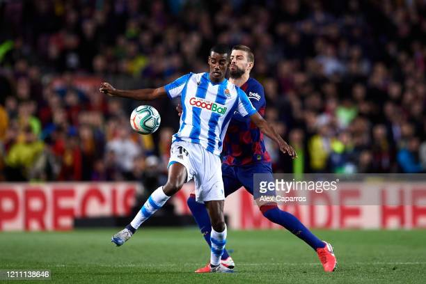 Alexander Isak of Real Sociedad controls the ball under pressure from Gerard Pique of FC Barcelona during the Liga match between FC Barcelona and...