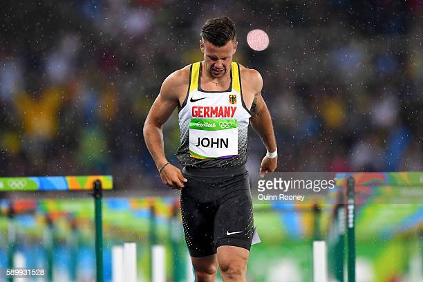 Alexander John of Germany reacts after being disqualified as rain falls following the Men's 110m Hurdles Round 1 Heat 1 on Day 10 of the Rio 2016...