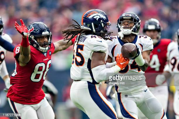 Alexander Johnson and Will Parks of the Denver Broncos try to intercept a pass during the second half of a game against the Houston Texans at NRG...
