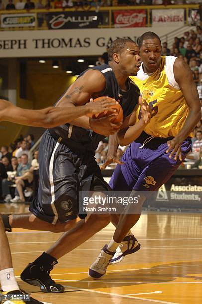 Alexander Johnson of the Memphis Grizzlies drives past Marcus Douthit of the Los Angeles Lakers during the 2006 Long Beach Summer League on July 15...