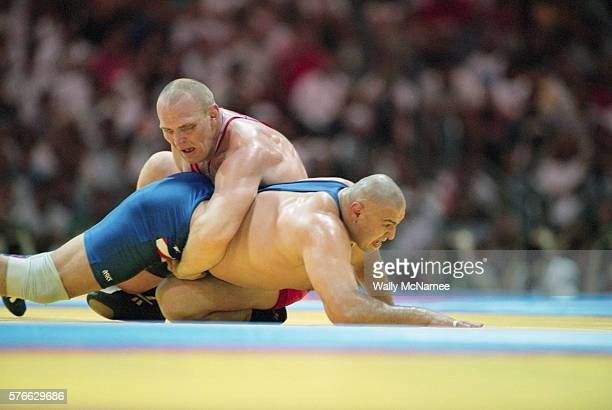Alexander Karelin of Russia holds down Matt Ghafarri of the USA as they compete for the gold medal in the super heavyweight GrecoRoman wrestling...