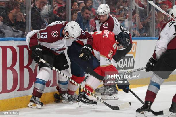 Alexander Kerfoot and Mikko Rantanen of the Colorado Avalanche battle for control of the puck with Alex Petrovic of the Florida Panthers at the BBT...