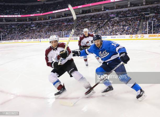Alexander Kerfoot of the Colorado Avalanche and Bryan Little of the Winnipeg Jets keep an eye on the play along the boards during first period action...