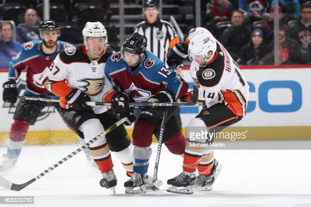 Alexander Kerfoot of the Colorado Avalanche battles for position against Nick Ritchie and Adam Henrique of the Anaheim Ducks at the Pepsi Center on...
