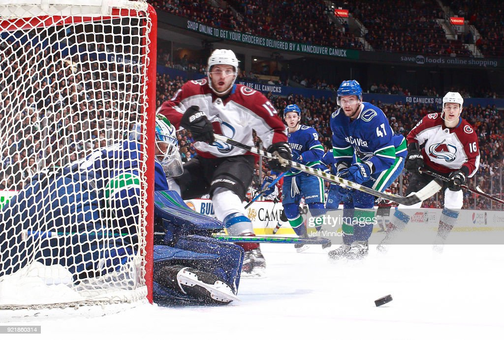 Alexander Kerfoot #13 of the Colorado Avalanche looks on as Anders Nilsson #31 of the Vancouver Canucks blocks a shot during their NHL game at Rogers Arena February 20, 2018 in Vancouver, British Columbia, Canada. Colorado won 5-4.