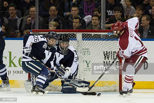 Alexander Kerfoot of the Harvard Crimson drives the net against Nicholas Weberg and Alex Lyon of the Yale Bulldogs on January 11 2014 at Madison...