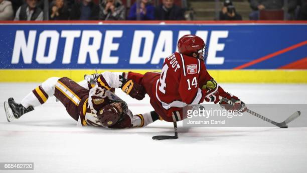 Alexander Kerfoot of the Harvard Crimson tries to get off a shot as he's grabbed by Alex Iafallo of the MinnesotaDuluth Bulldogs during game one of...