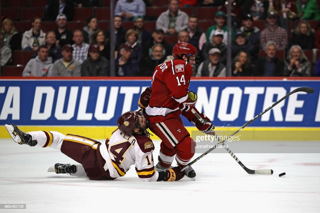 Alexander Kerfoot #14 of the Harvard Crimson tries to get off a shot as he's grabbed by Alex Iafallo #14 of the Minnesota-Duluth Bulldogs during game one of the 2017 NCAA Division I Men's Hockey Championship Semifinal at the United Center on April 6, 2017 in Chicago, Illinois.