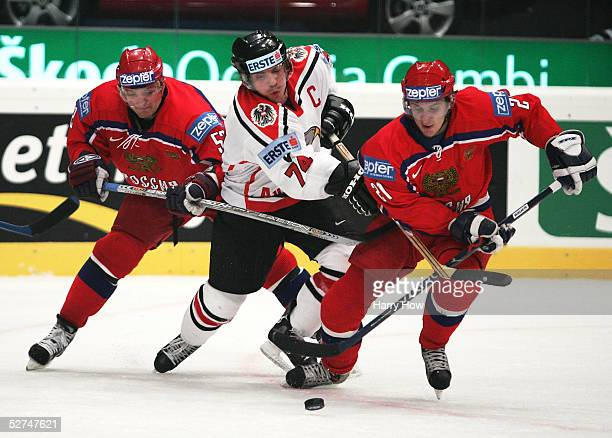 Alexander Kharitonov and Andrey Markov of Russia pinch Dieter Kalt of Austria in the IIHF World Men's Championships preliminary round game at Wiener...