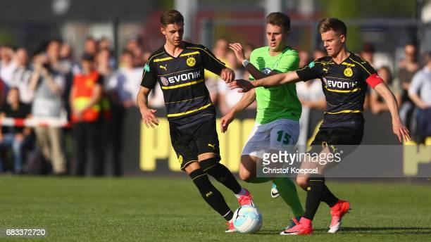 Alexander Laukart of Dortmund and Dzenis Burnic of Dortmund challenge Yannik Moeker of Wolfsburg during the U19 German Championship Semi Final second...