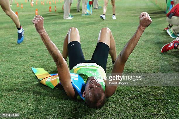 Alexander Lesun of Russia celebrates on the floor after crossing the line to win gold in the Modern Pentathlon on Day 15 of the Rio 2016 Olympic...