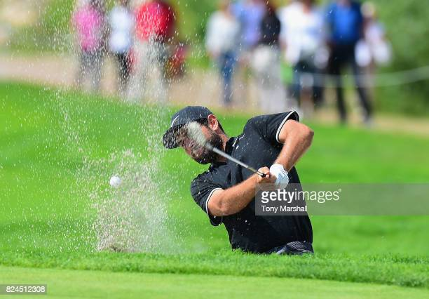 Alexander Levy of France plays out of a bunker onto the 11th green during the Porsche European Open Day Four at Green Eagle Golf Course on July 30...
