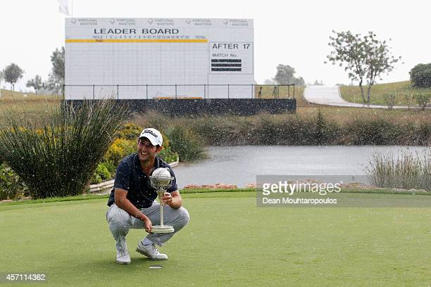 Alexander Levy of France poses with the trophy as the rain starts again on the 18th green after winning the Portugal Masters at the Oceanico Victoria...