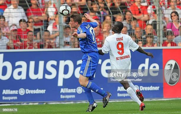 Alexander Madlung of Wolfsburg jumps for a header against Papiss Cisse of Freiburg during the Bundesliga match between SC Freiburg and VfL Wolfsburg...