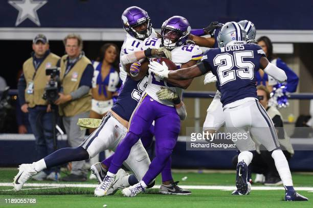 Alexander Mattison of the Minnesota Vikings gets tackled by Leighton Vander Esch and Xavier Woods of the Dallas Cowboys at AT&T Stadium on November...