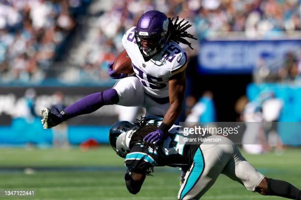 Alexander Mattison of the Minnesota Vikings hurdles Donte Jackson of the Carolina Panthers during the fourth quarter at Bank of America Stadium on...