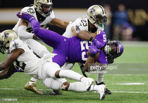 Alexander Mattison of the Minnesota Vikings is tackled by Marshon Lattimore and Chauncey GardnerJohnson of the New Orleans Saints during the first...
