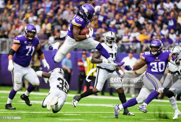 Alexander Mattison of the Minnesota Vikings leaps over defender Curtis Riley of the Oakland Raiders for a touchdown in the third quarter of the game...