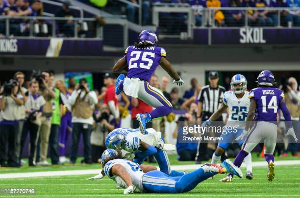 Alexander Mattison of the Minnesota Vikings leaps over two Detroit Lions defenders while running with the ball in the second quarter of the game at...
