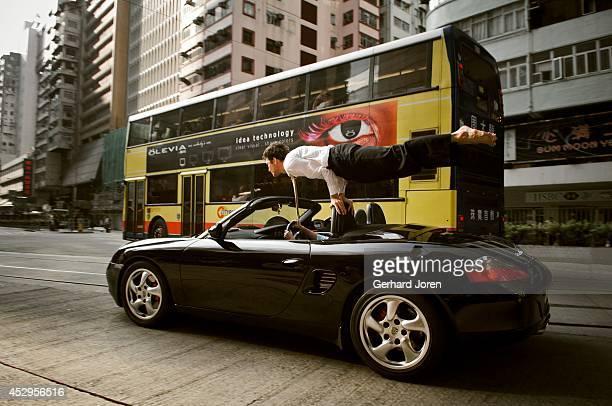 Alexander Medin a Norwegian yoga teacher living in Hong Kong performs a yoga pose on a moving car in Wan Chai Hong Kong MODEL RELEASED