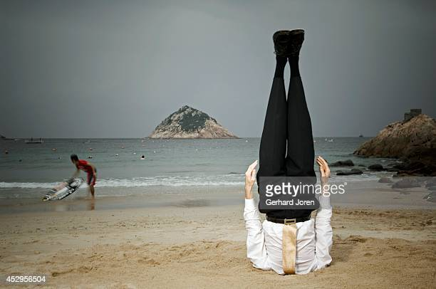 Alexander Medin a Norwegian yoga teacher performs a yoga pose controling his breath for 5 minutes while standing on his head in the sand on a beach...