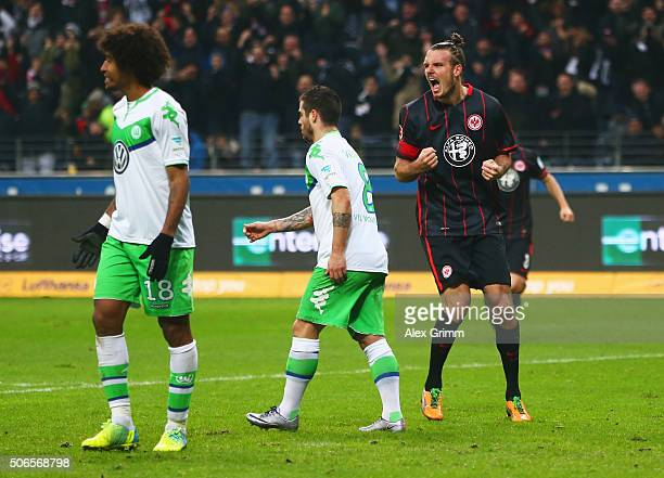 Alexander Meier of Eintracht Frankfurt celebrates as he scores their first and equalising goal as Dante and Vierinha of VfL Wolfsburg look dejected...