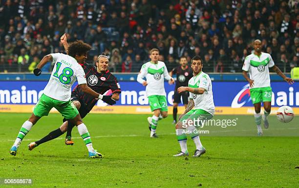 Alexander Meier of Eintracht Frankfurt shoots past Dante and Vierinha of VfL Wolfsburg to score their first and equalising goal during the Bundesliga...